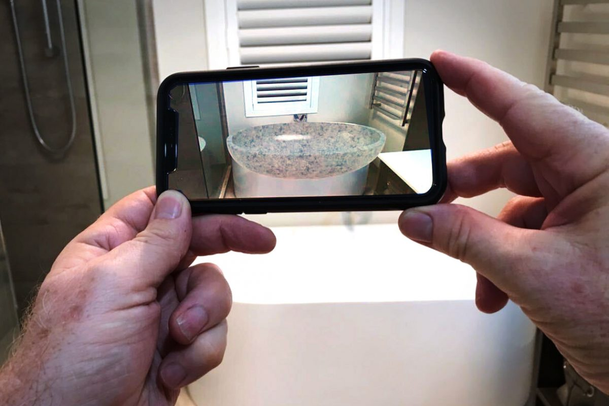 WEB BASED AUGMENTED REALITY Company X augmented reality specialist Lance Bauerfeind demonstrates how Web AR can be used to overlay a AR model of a new bath over the old bath on his smartphone